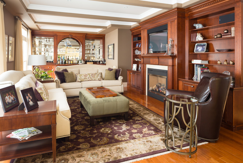 Inspiration for a mid-sized timeless medium tone wood floor family room remodel in Toronto with beige walls, a standard fireplace and a wall-mounted tv
