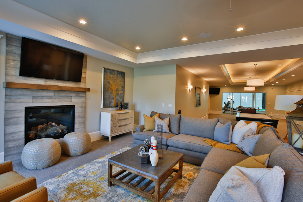 Large transitional open concept carpeted game room photo in Salt Lake City with beige walls, a standard fireplace, a wood fireplace surround and a wall-mounted tv