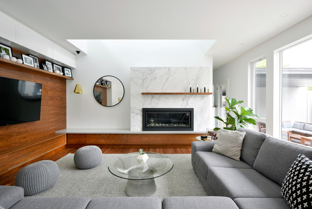 Inspiration for a contemporary medium tone wood floor family room remodel in Ottawa with white walls, a ribbon fireplace, a stone fireplace and a media wall