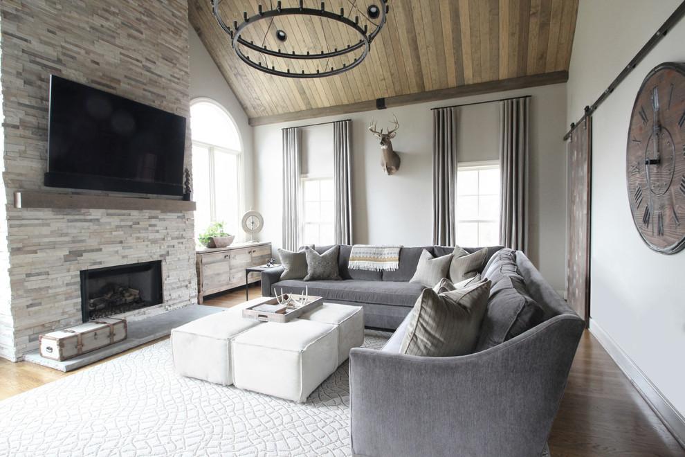 ナッシュビルの広いトランジショナルスタイルのおしゃれなファミリールーム (ベージュの壁、無垢フローリング、標準型暖炉、石材の暖炉まわり、壁掛け型テレビ) の写真