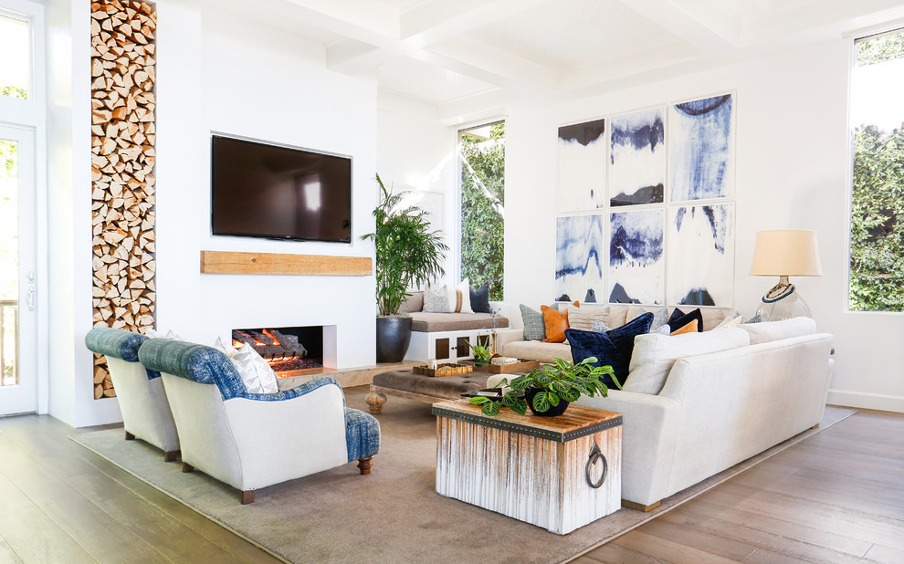 Large beach style open concept dark wood floor family room photo in Orange County with white walls, a ribbon fireplace, a plaster fireplace and a wall-mounted tv