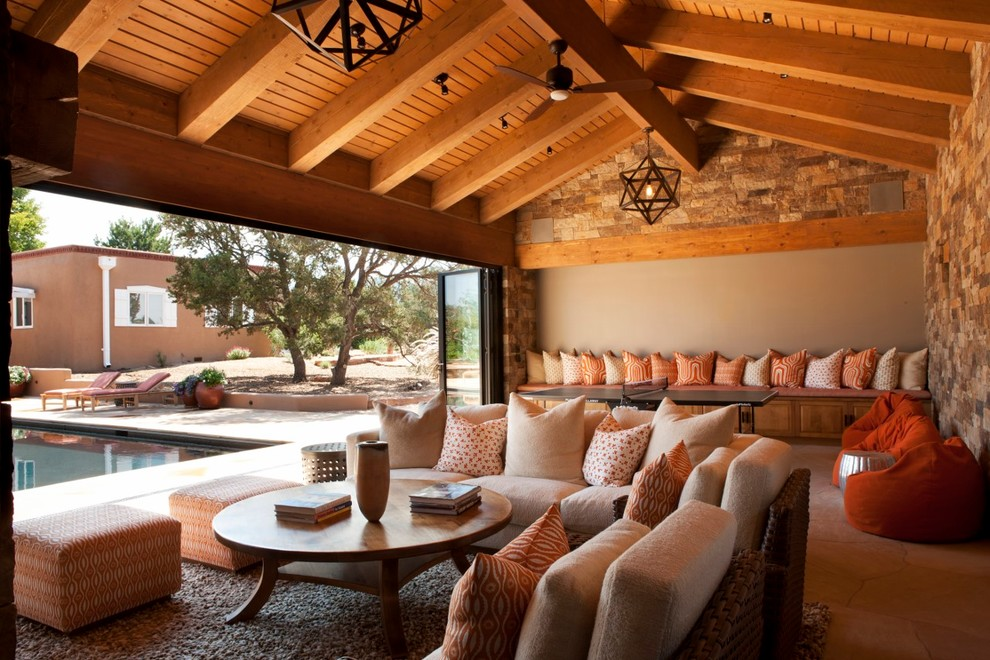 Family room - large rustic open concept carpeted family room idea in Albuquerque with multicolored walls, a standard fireplace, a stone fireplace and a media wall