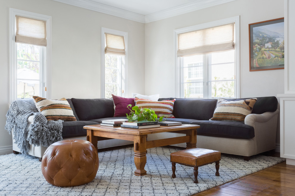 Example of a mid-sized transitional enclosed medium tone wood floor and brown floor family room design in Los Angeles with beige walls and no fireplace