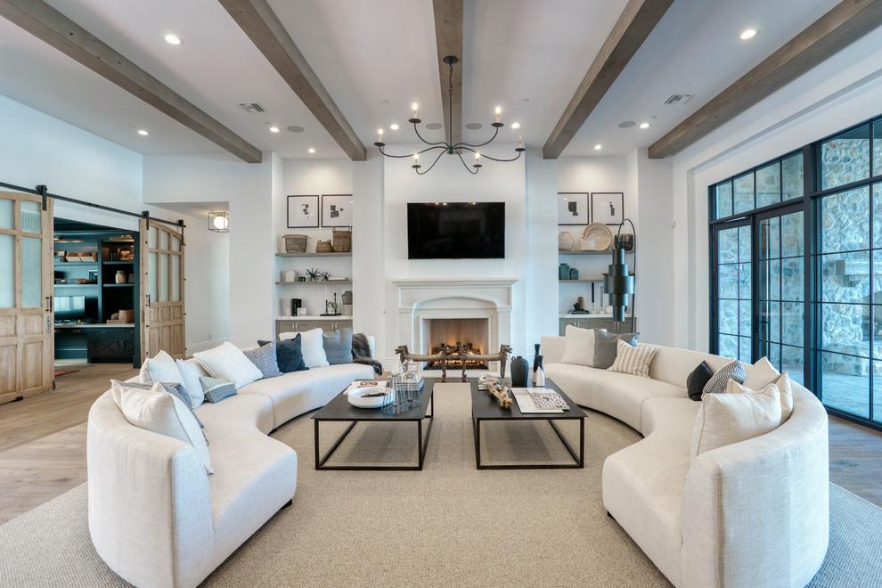 Cette image montre une grand salle de séjour traditionnelle fermée avec un mur blanc, un sol en bois clair, une cheminée standard, un téléviseur fixé au mur et un sol beige.