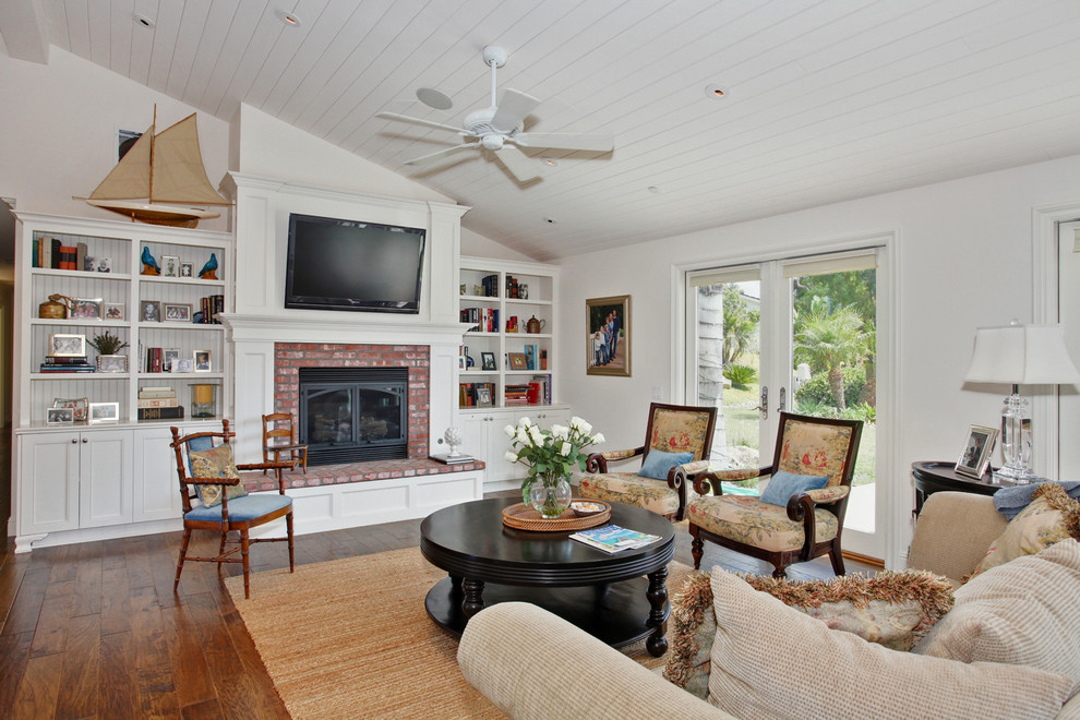 Elegant medium tone wood floor family room photo in San Diego with white walls, a standard fireplace, a brick fireplace and a wall-mounted tv