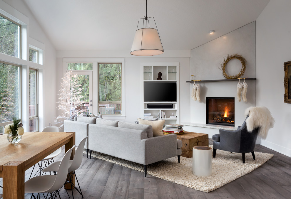Inspiration for a large scandinavian open concept dark wood floor and gray floor family room remodel in Portland with white walls, a corner fireplace, a concrete fireplace and a media wall