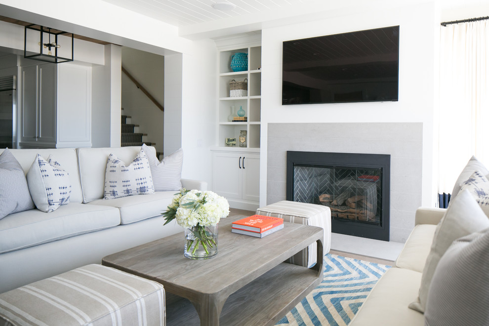 Example of a beach style open concept family room design in Orange County with white walls, a standard fireplace and a stone fireplace