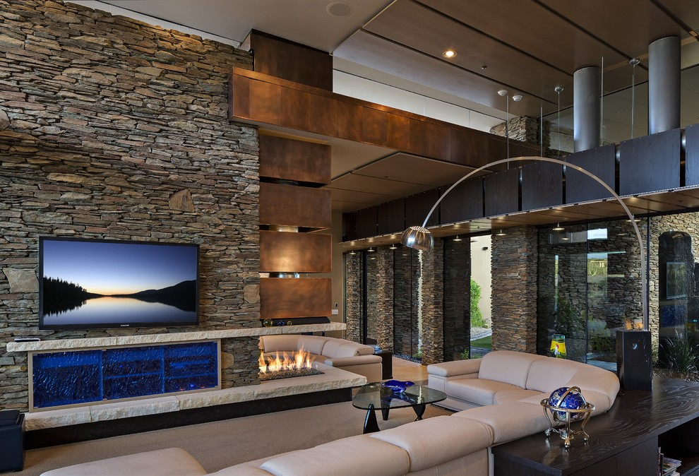 Inspiration for a large contemporary open concept concrete floor and beige floor family room remodel in Phoenix with beige walls, a wall-mounted tv, a corner fireplace and a stone fireplace