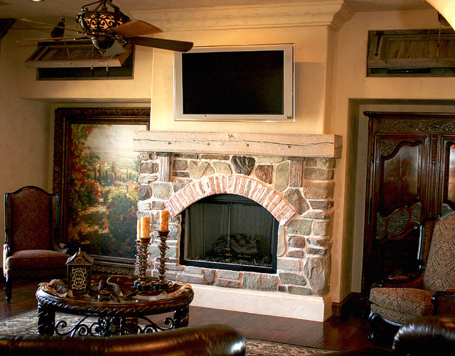Family room - rustic dark wood floor family room idea in Austin with a standard fireplace and a stone fireplace