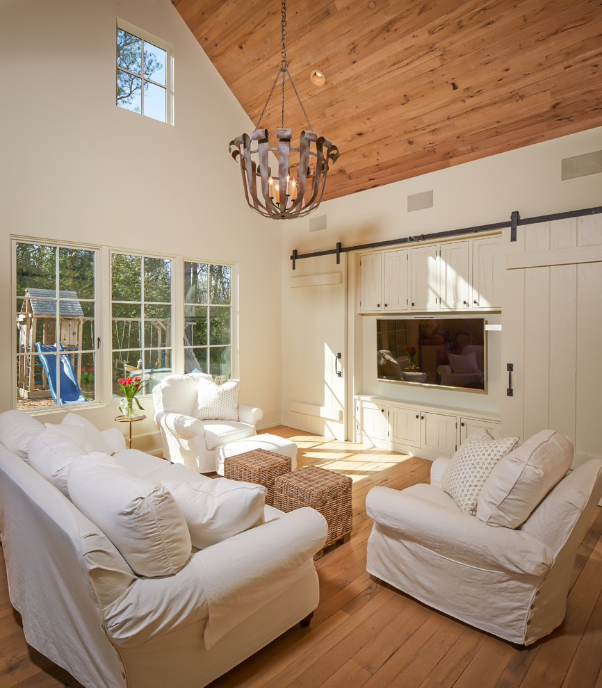 Mid-sized elegant enclosed medium tone wood floor and brown floor family room photo in Houston with a media wall, white walls and no fireplace