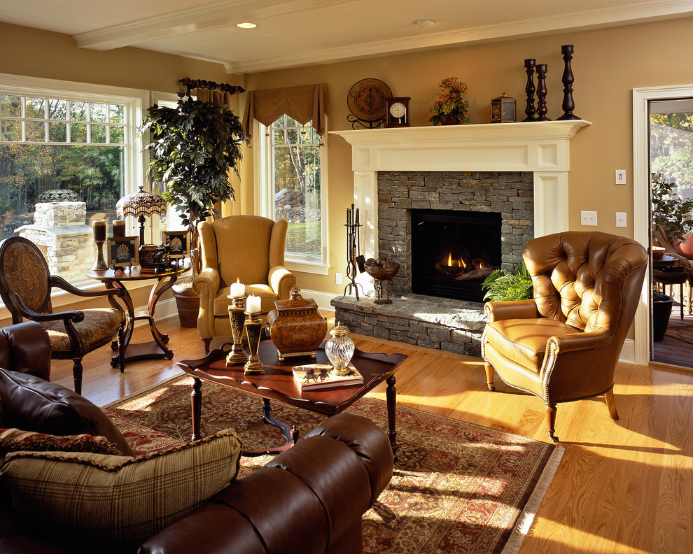 Family room - traditional medium tone wood floor family room idea in New York with beige walls, a standard fireplace, a stone fireplace and no tv