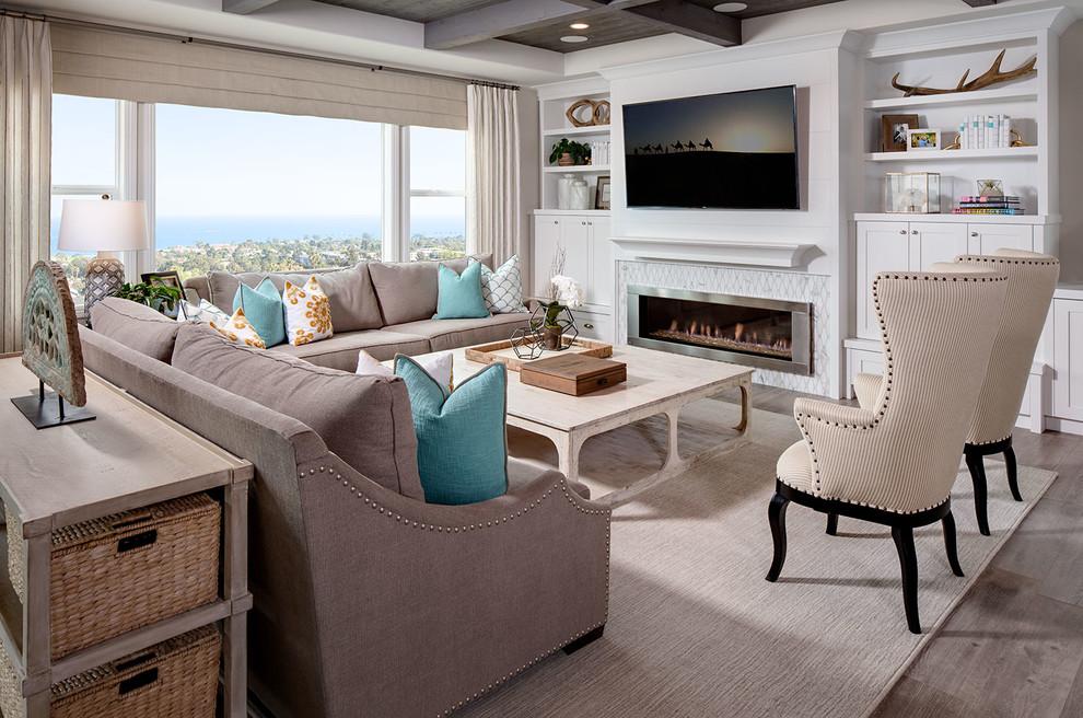 Diseño de sala de estar abierta, costera, grande, con televisor colgado en la pared, paredes beige, chimenea lineal, marco de chimenea de baldosas y/o azulejos y suelo de madera clara