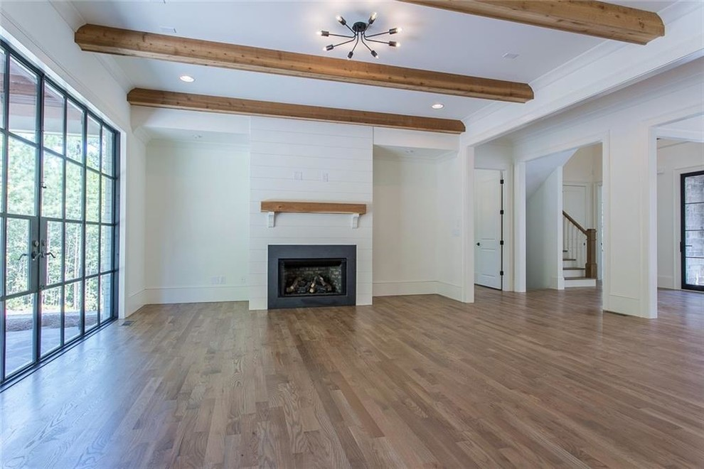 Family room - large transitional open concept light wood floor and gray floor family room idea in Atlanta with white walls, a standard fireplace, a stone fireplace and a wall-mounted tv