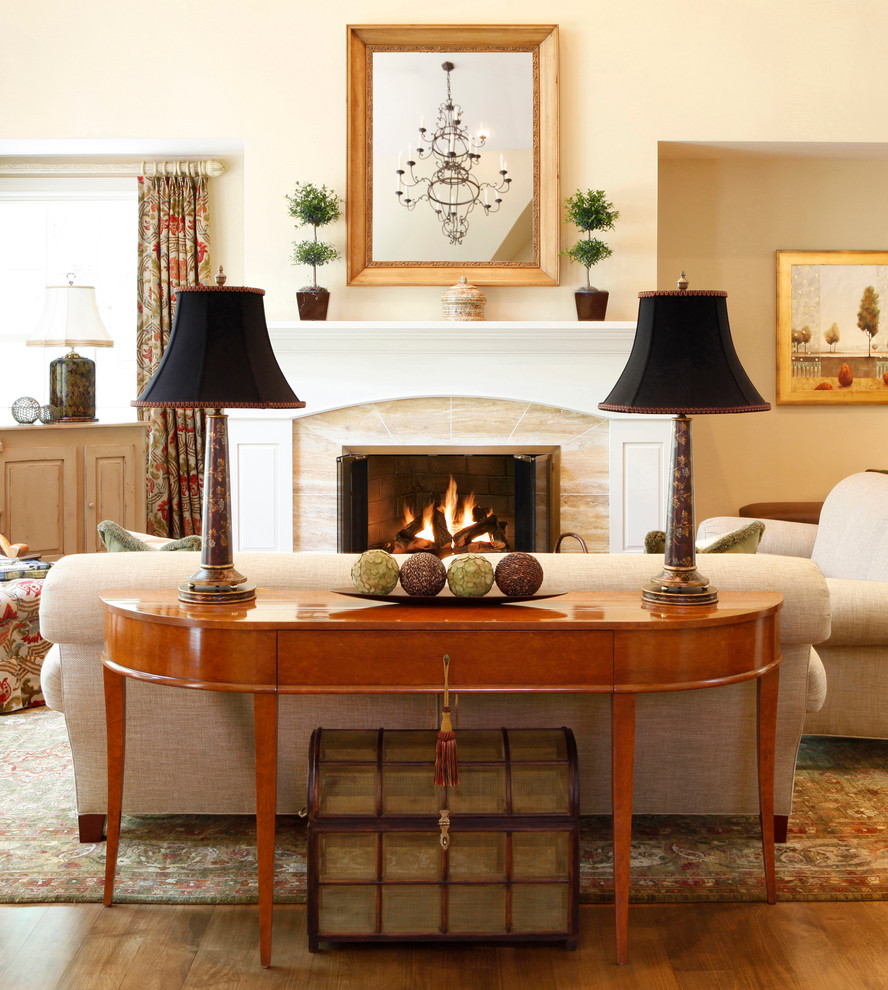 Inspiration for a timeless medium tone wood floor family room remodel in Philadelphia with beige walls, a standard fireplace and no tv
