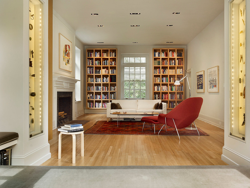Trendy medium tone wood floor family room library photo in Philadelphia with beige walls, a standard fireplace and no tv