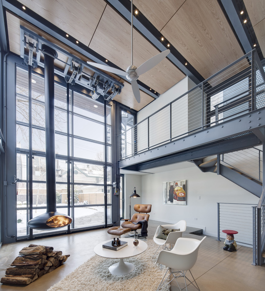 Example of a small urban enclosed concrete floor family room design in Chicago with white walls and a hanging fireplace