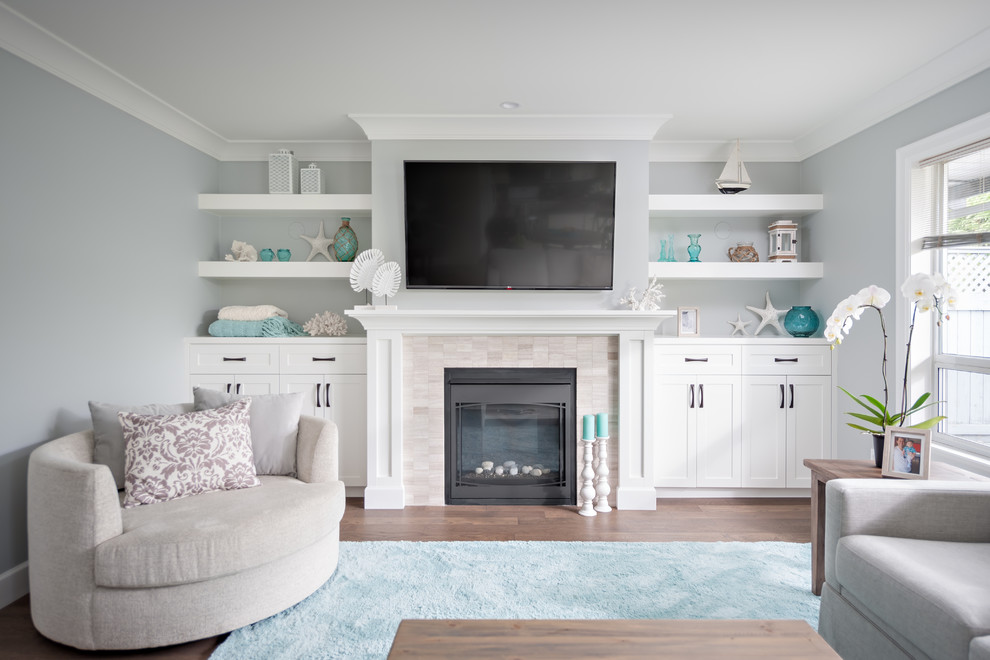 Mid-sized beach style dark wood floor family room photo in Vancouver with gray walls, a standard fireplace, a stone fireplace and a media wall