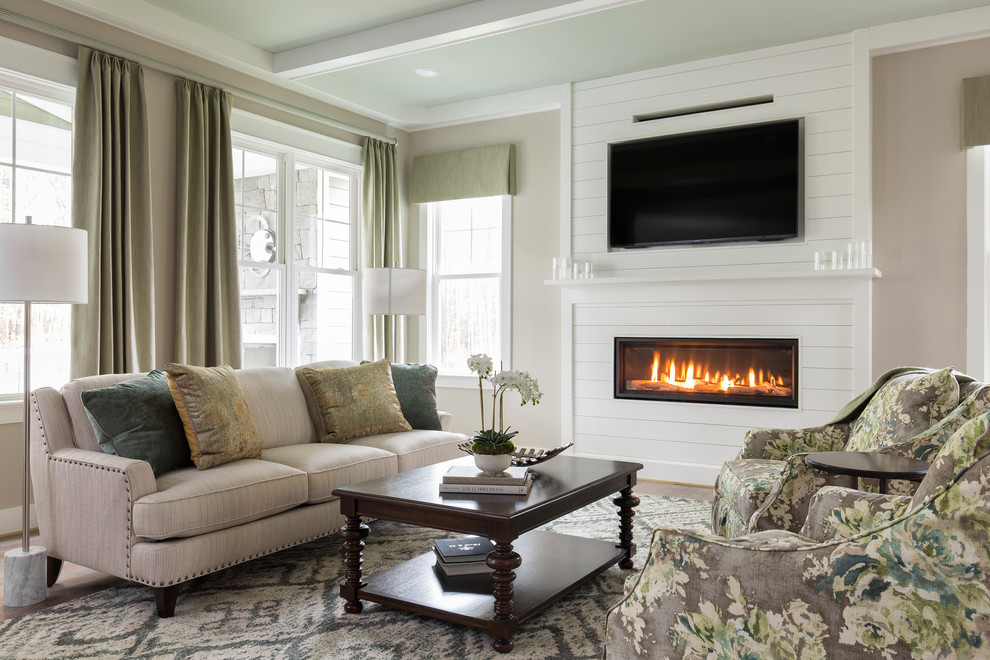 Inspiration for a timeless medium tone wood floor and brown floor family room remodel in Richmond with beige walls, a ribbon fireplace, a wood fireplace surround and a wall-mounted tv