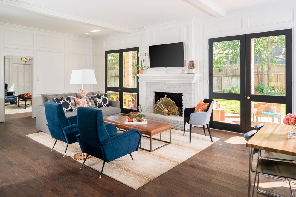 Family room - transitional dark wood floor and brown floor family room idea in Houston with white walls, a standard fireplace, a brick fireplace and a wall-mounted tv