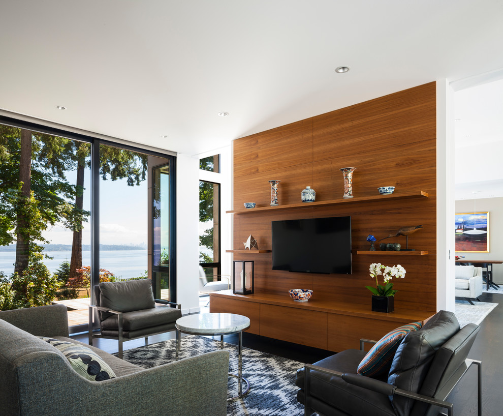 Example of a trendy open concept dark wood floor and black floor family room design in Seattle with white walls and a wall-mounted tv