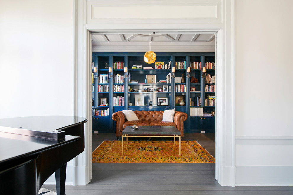 Family room library - large traditional open concept medium tone wood floor and gray floor family room library idea in San Francisco with blue walls