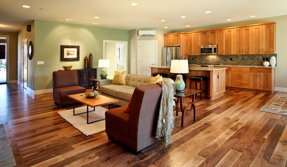 Example of a trendy open concept medium tone wood floor and brown floor family room design in Portland with green walls