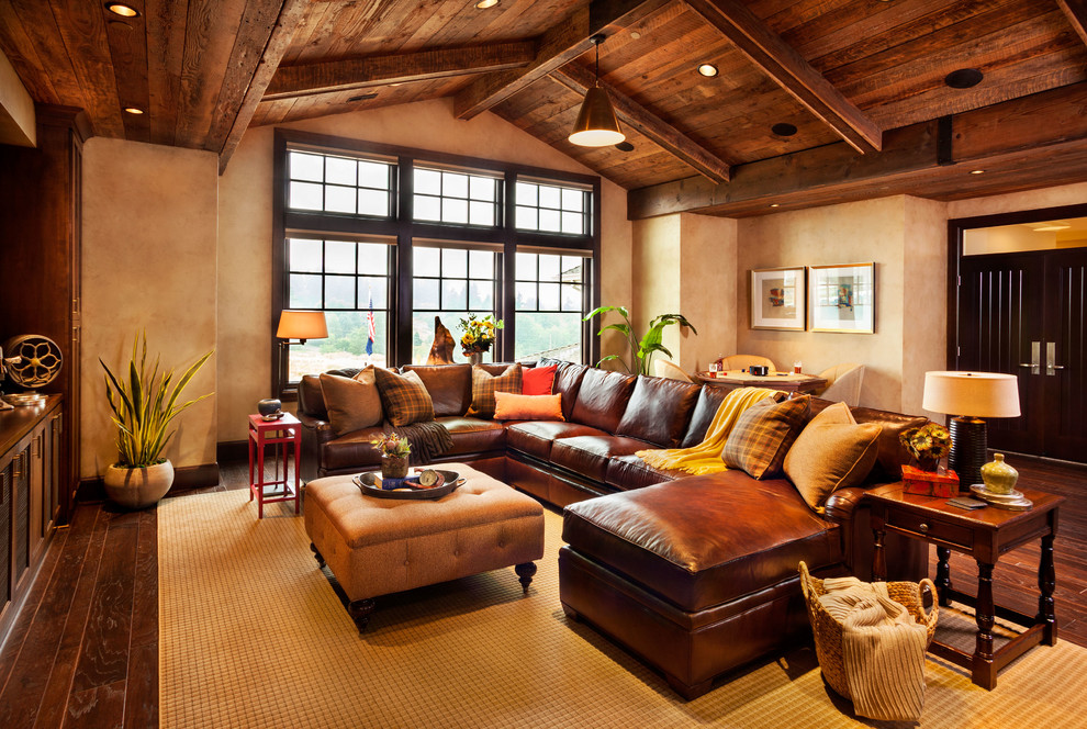 Inspiration for a huge rustic enclosed dark wood floor family room remodel in Portland with beige walls