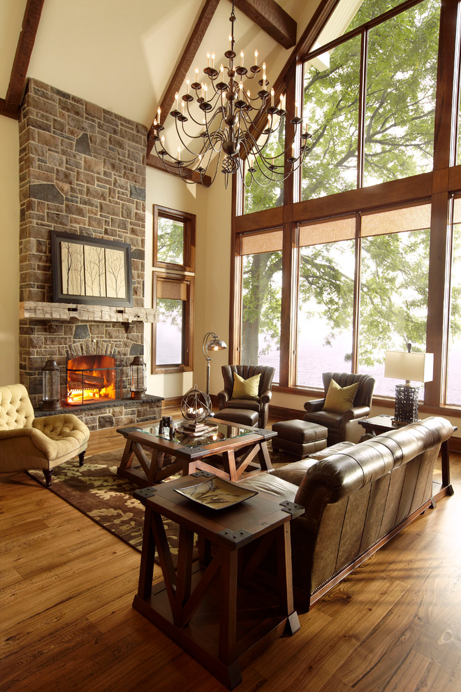 Example of a large mountain style medium tone wood floor family room design in Toronto with a stone fireplace, beige walls and a standard fireplace