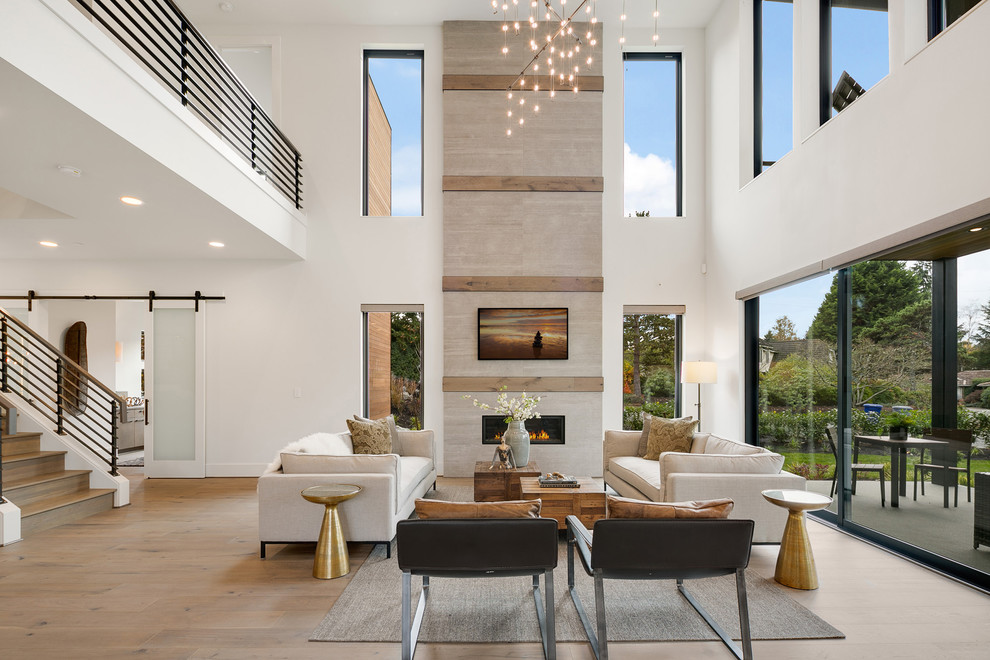 Example of a large trendy open concept medium tone wood floor and beige floor family room design in Seattle with white walls, a standard fireplace, a wall-mounted tv and a stone fireplace