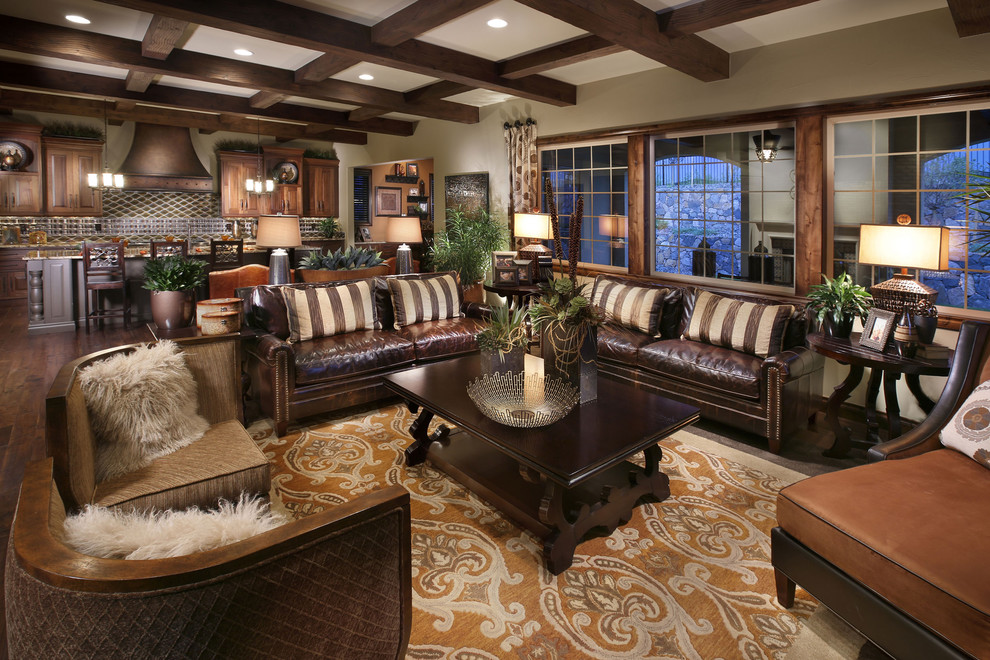 Example of a tuscan open concept dark wood floor family room design in Denver with beige walls