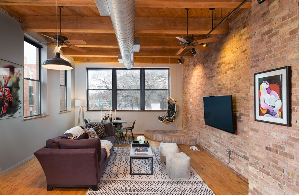 Large urban open concept medium tone wood floor family room photo in Milwaukee with a wall-mounted tv, gray walls and no fireplace