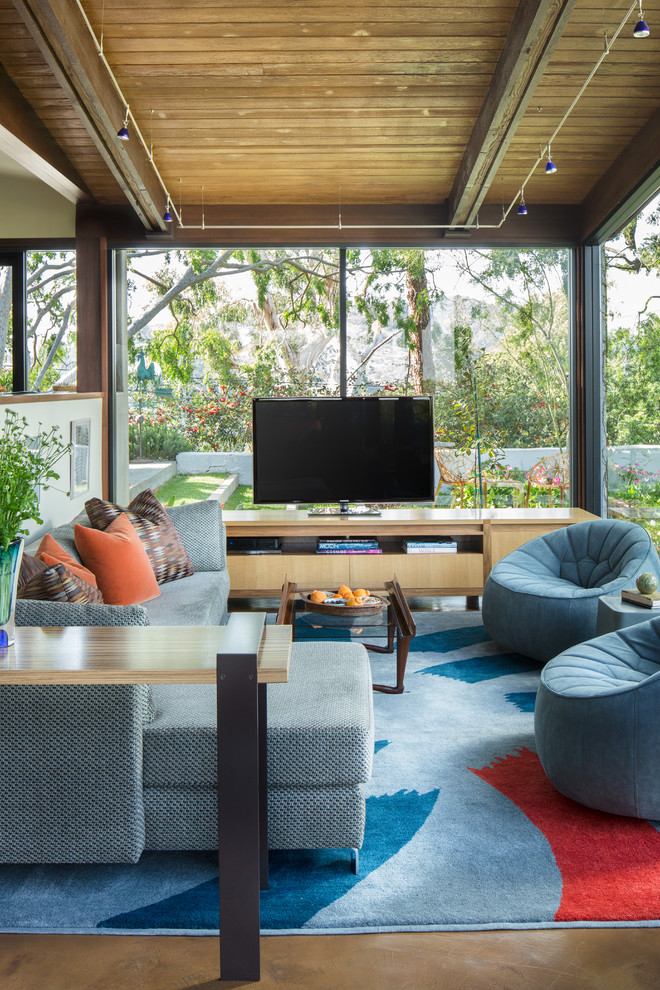 Inspiration for a large contemporary open concept concrete floor and blue floor family room remodel in Los Angeles with a tv stand