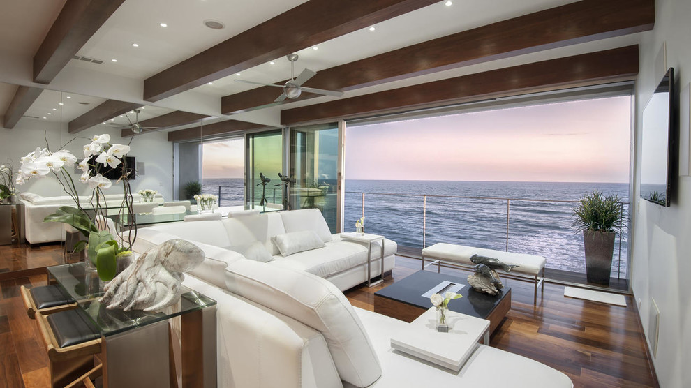 Example of a beach style open concept dark wood floor family room design in Los Angeles with white walls, no fireplace and a wall-mounted tv