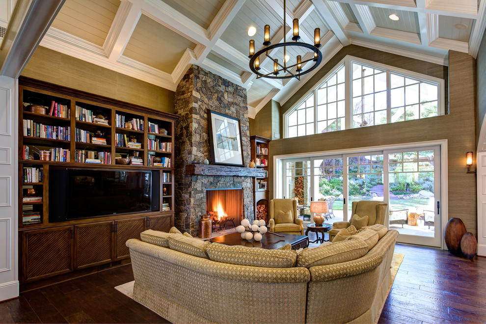 Inspiration for a large timeless open concept dark wood floor and brown floor family room library remodel in Orange County with beige walls, a standard fireplace, a stone fireplace and a media wall
