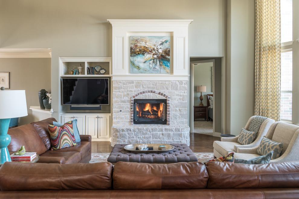 ダラスの中くらいのトランジショナルスタイルのおしゃれなオープンリビング (グレーの壁、無垢フローリング、標準型暖炉、石材の暖炉まわり、埋込式メディアウォール、茶色い床) の写真