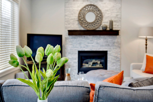 Example of a small transitional enclosed dark wood floor family room design in Calgary with gray walls, a standard fireplace, a stone fireplace and a corner tv