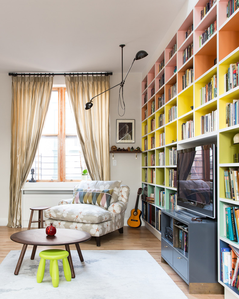 Example of a 1950s medium tone wood floor family room library design in New York with gray walls and a media wall