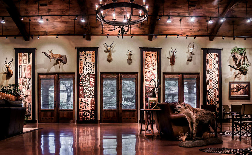 Huge mountain style enclosed concrete floor and brown floor game room photo in Austin with beige walls