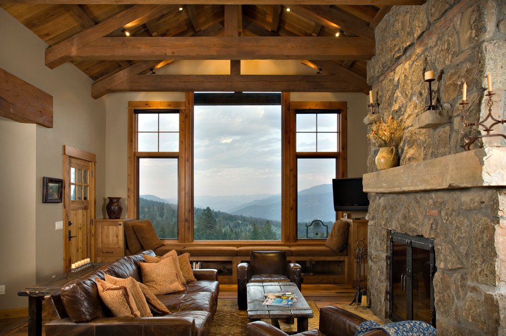 Example of a mountain style family room design in Other with a stone fireplace