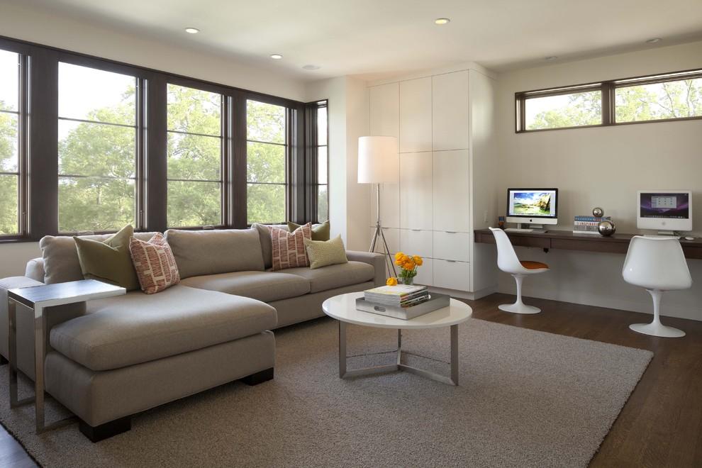 Example of a trendy medium tone wood floor family room design in Minneapolis with beige walls