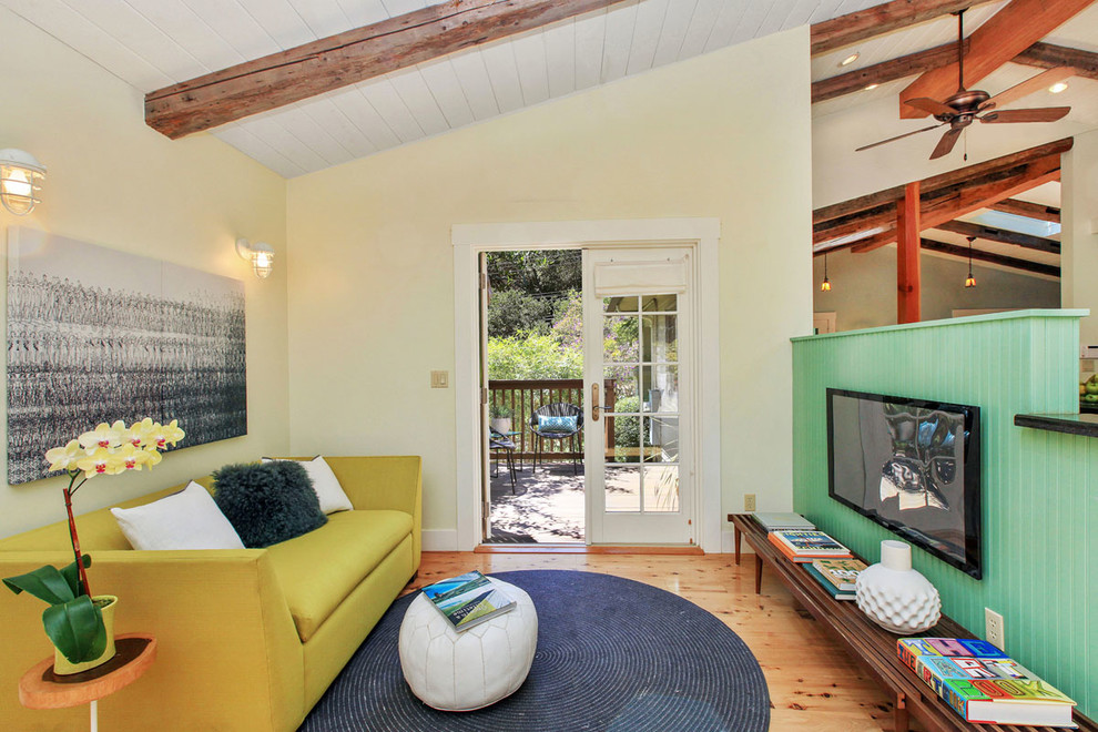 Inspiration for a small farmhouse open concept medium tone wood floor family room remodel in San Francisco with yellow walls, no fireplace and a wall-mounted tv