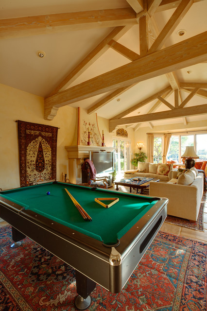 Vaulted ceiling family room with a pool table mediterranean family room