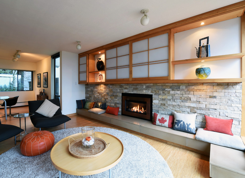 Example of a mid-sized trendy enclosed bamboo floor and beige floor family room design in Vancouver with white walls, a standard fireplace, a stone fireplace and a media wall