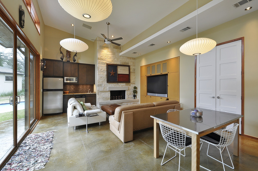 Inspiration for a contemporary concrete floor family room remodel in Austin with a stone fireplace