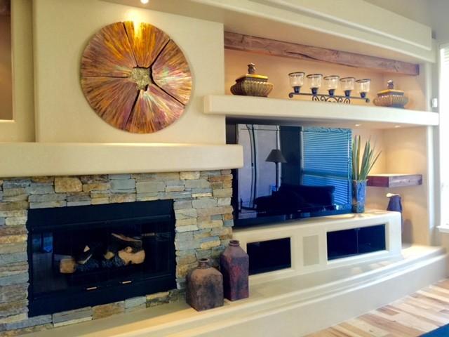 Foto di un grande soggiorno minimal aperto con pareti beige, parquet chiaro, camino classico, cornice del camino in pietra, TV autoportante e pavimento marrone