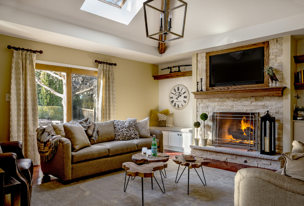 Inspiration for a mid-sized rustic family room remodel in Chicago with beige walls, a standard fireplace, a stone fireplace and a wall-mounted tv
