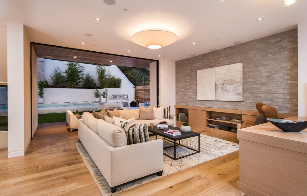 Example of a huge trendy open concept light wood floor family room library design in Los Angeles with gray walls and a wall-mounted tv