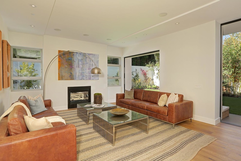 Inspiration for a large modern open concept medium tone wood floor family room library remodel in Los Angeles with white walls, a two-sided fireplace and a metal fireplace