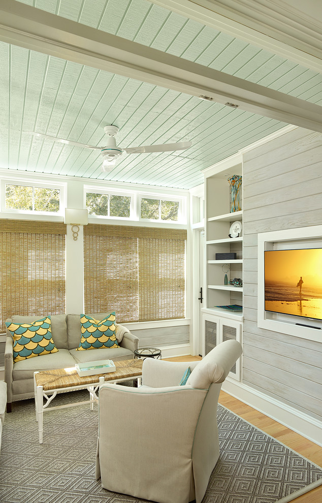Inspiration for a coastal light wood floor family room remodel in Charleston with gray walls and a wall-mounted tv