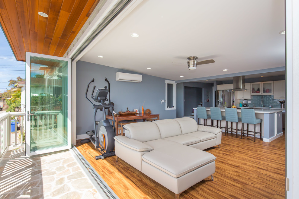Inspiration for a large transitional open concept light wood floor family room remodel in Hawaii with blue walls, no fireplace and a tv stand